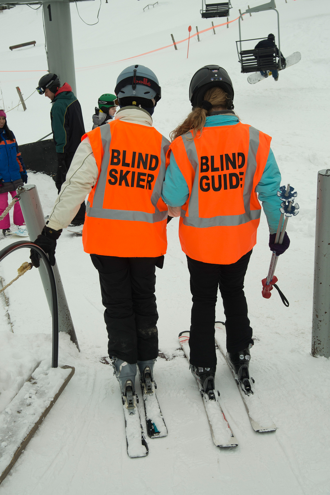 Blind guide helping blind skier onto ski lifts