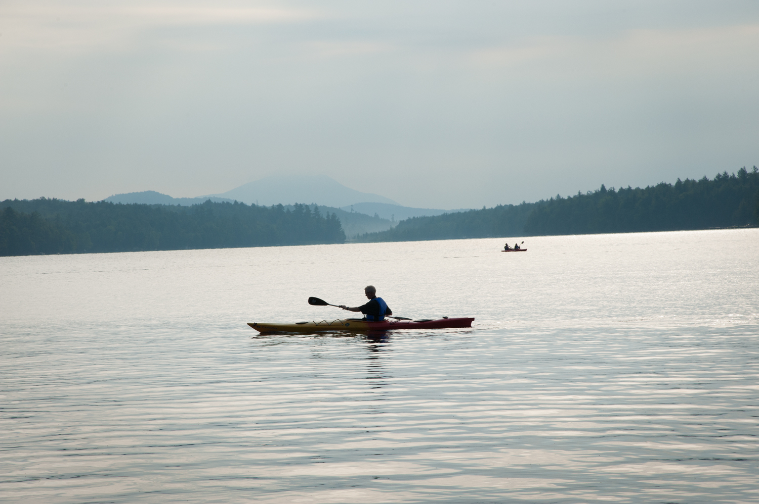 Kayaker on Raquette Lake with Blue Mountain in background